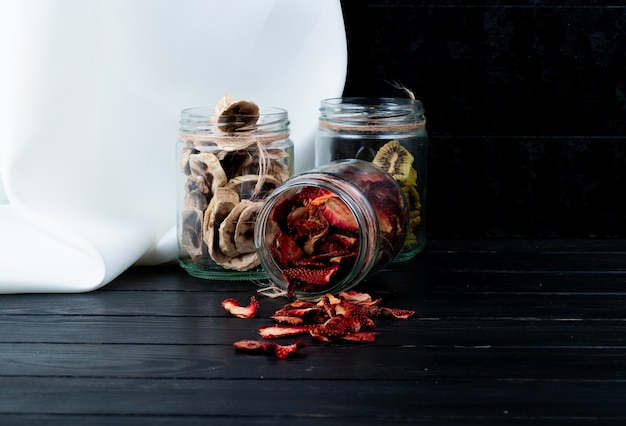Vue latérale de diverses tranches de fruits secs dans des bocaux en verre banane fraise et kiwi sur fond noir avec copie espace