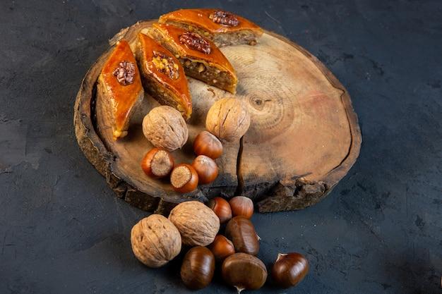 Vue latérale du baklava azerbaïdjanais traditionnel avec des noix entières sur planche de bois sur fond noir