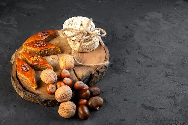 Vue latérale du baklava azerbaïdjanais traditionnel avec des pains de riz aux noix sur planche de bois sur fond noir