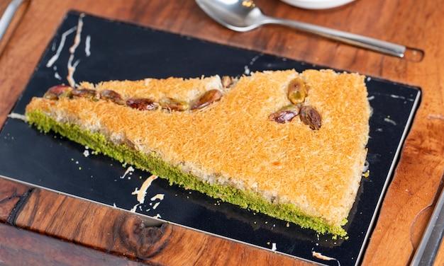 Vue latérale du baklava turc avec pistache sur une planche de bois
