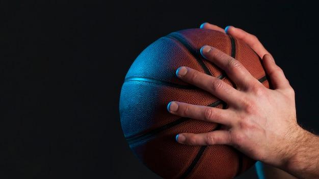 Vue latérale du basket-ball a tenu mon joueur masculin