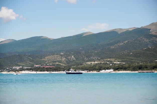 Vue latérale du bateau de chalutier de pêche sans personnes dans la baie de la mer noire sur la plage