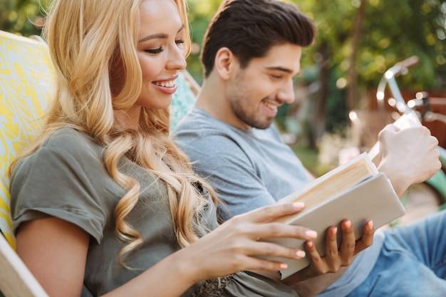 Vue latérale du beau jeune couple souriant assis ensemble sur des chaises longues et lire des livres à l'extérieur