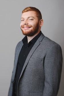 Vue latérale du beau mec à la barbe rousse en costume élégant souriant joyeusement et regardant la caméra en se tenant debout sur fond gris