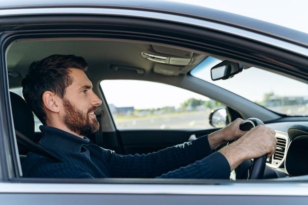 Vue latérale du bel homme d'affaires conduisant une voiture avant d'acheter. un homme élégant et séduisant en affaires ferme la voiture au volant. notion de transport