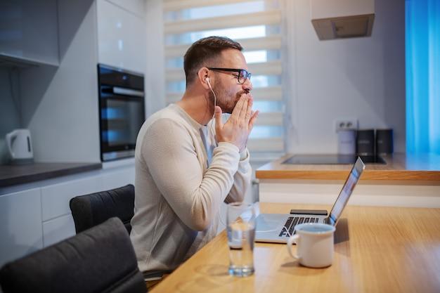 Vue latérale du bel homme caucasien non rasé ayant un appel vidéo avec sa petite amie et lui envoyant des baisers. dans les écouteurs d'oreilles, sur le bureau sont un verre d'eau, une tasse de café et un ordinateur portable. intérieur de cuisine.
