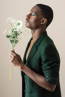 Vue latérale du bel homme posant en blazer et portant du maquillage tout en tenant des fleurs