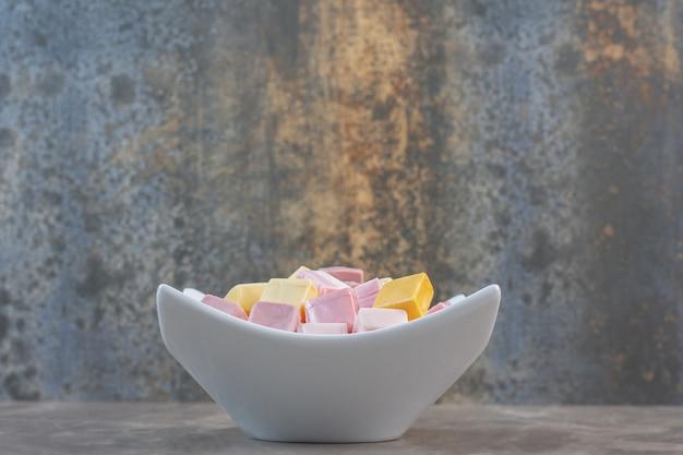 Vue latérale du bol blanc plein de bonbons sucrés sur fond gris.