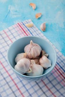 Vue latérale du bol de bulbes d'ail avec des gousses d'ail sur un tissu écossais sur fond bleu