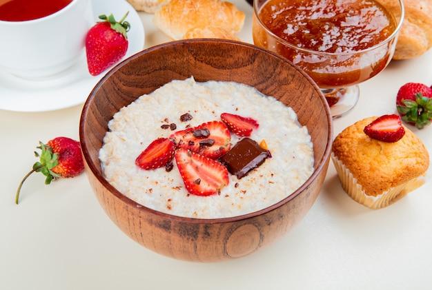 Vue latérale du bol de flocons d'avoine avec du chocolat au fromage cottage et des fraises avec de la confiture de cupcakes, des rouleaux de thé autour d'un tableau blanc