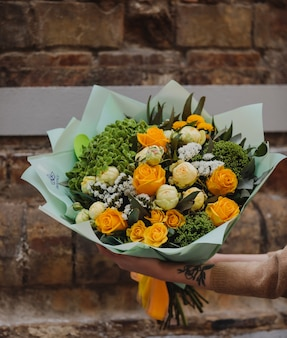 Vue latérale du bouquet de roses de couleur jaune pivoines de couleur blanche eustomas et fleurs de mur de trachelium sur mur de brique mur