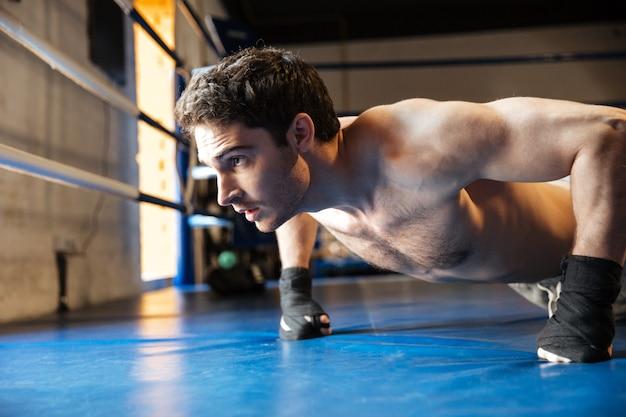 Vue latérale du boxeur concentré faisant des pompes