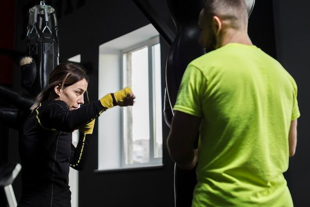 Vue latérale du boxeur féminin pratiquant avec un entraîneur masculin en t-shirt