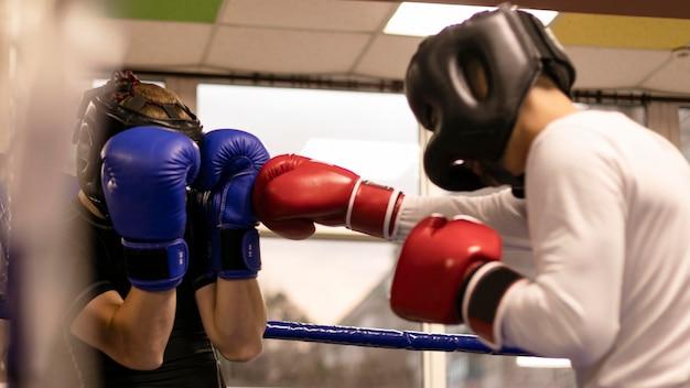 Vue latérale du boxeur masculin avec casque pratiquant dans le ring