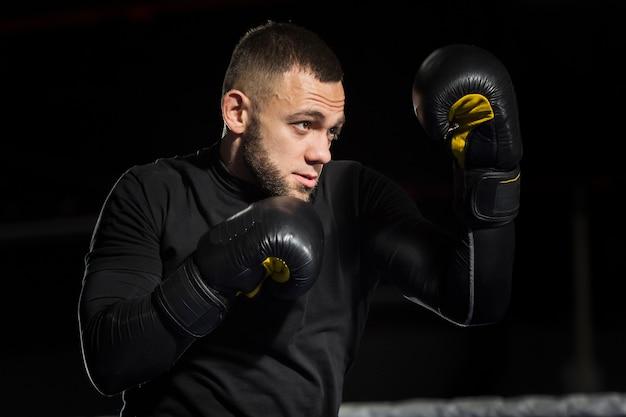 Vue latérale du boxeur posant dans des gants de protection