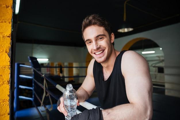 Vue latérale du boxeur souriant se détendre dans le ring de boxe