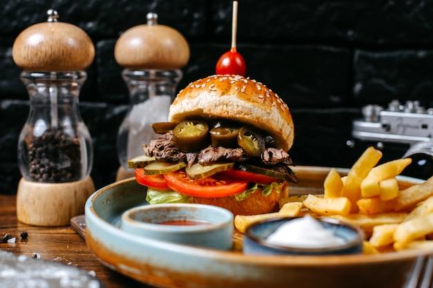 Vue latérale du burger avec des cornichons de viande de boeuf et des tomates servies avec des frites et des sauces sur fond noir