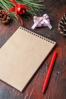 Vue latérale du cadeau et du cadeau de cône de conifère de stylo de cahier à spirale sur le fond foncé