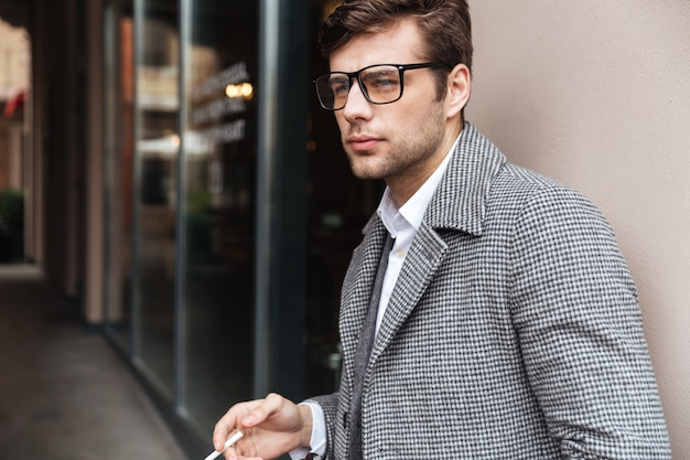 Vue latérale du calme homme d'affaires à lunettes
