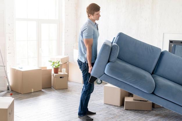Vue latérale du canapé de manipulation de l'homme tout en se préparant à déménager