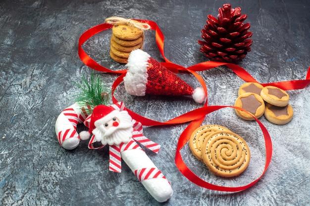 Vue latérale du chapeau de père noël et des biscuits-cadeaux de cône de conifère rouge chocolat cornel sur une surface sombre