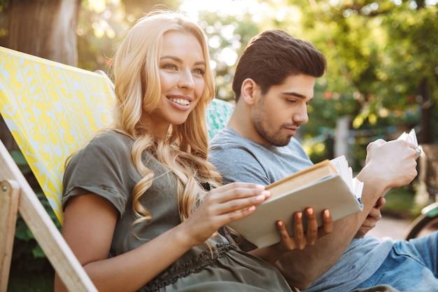 Vue latérale du charmant jeune couple heureux assis ensemble sur des chaises longues et lire des livres à l'extérieur