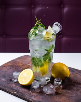 Vue latérale du cocktail mojito avec de la glace et du citron sur une planche de bois