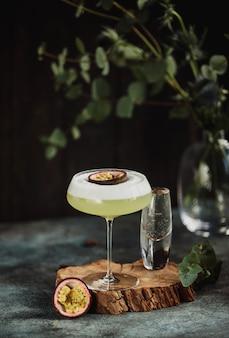 Vue latérale du cocktail tropical frais avec des fruits de la passion sur un support en bois