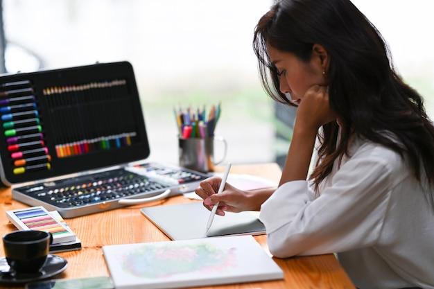 Vue latérale du concepteur créatif tenant un stylet et travaillant avec une tablette numérique au bureau.
