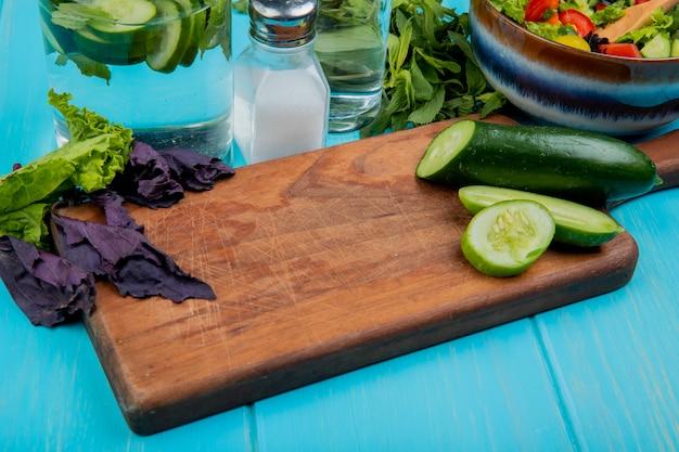 Vue latérale du concombre coupé et tranché sur une planche à découper avec de la laitue basilic, de la salade de légumes à la menthe, de l'eau détox et du sel sur une table bleue