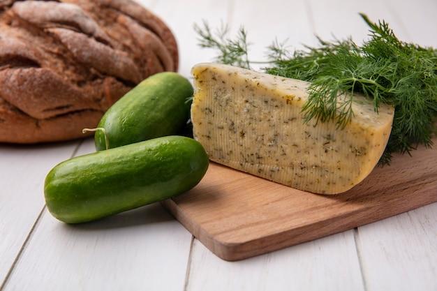 Vue latérale du concombre avec une miche de pain noir avec du fromage et de l'aneth sur fond blanc