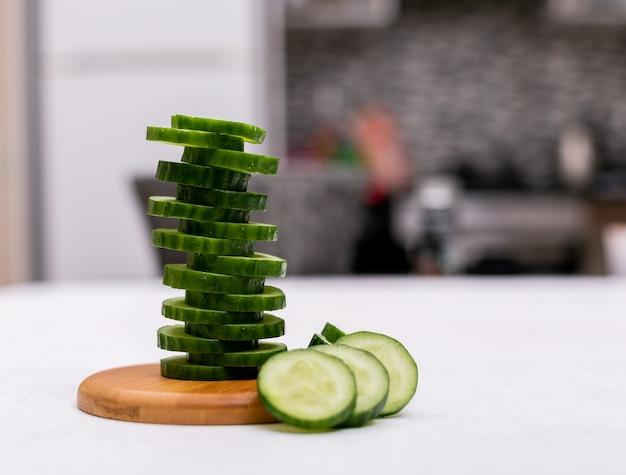 Vue latérale du concombre en tranches sur une planche de bois dans la cuisine