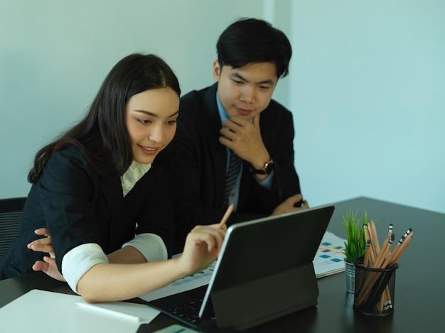Vue latérale du conseil de l'équipe commerciale sur leur projet avec tablette et paperasse dans la salle de bureau