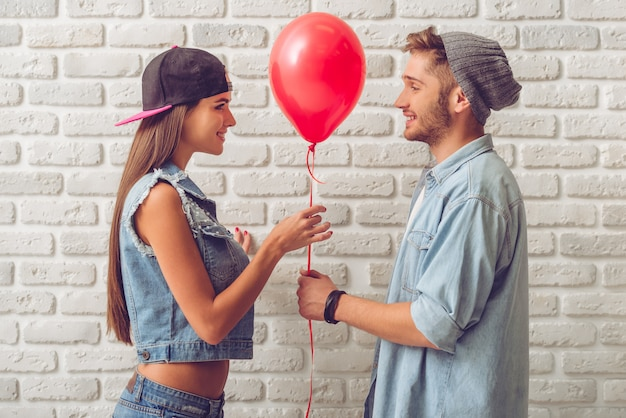 Vue latérale du couple d'adolescents élégant en vêtements de jean.