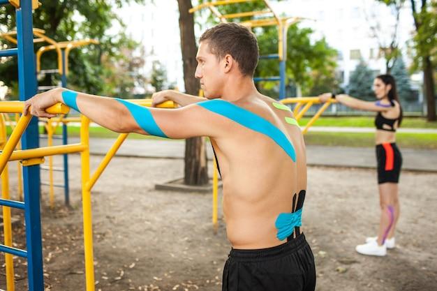 Vue latérale du couple d'athlètes caucasiens avec bande élastique de kinésiologie sur les corps, homme méconnaissable et femme brune s'entraînant à l'aide de barres au terrain de sport.