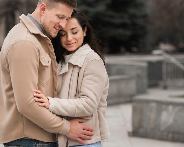 Vue latérale du couple embrassé à l'extérieur