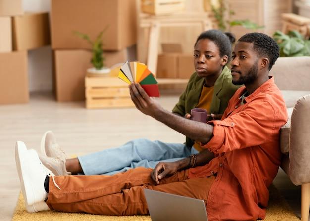 Vue latérale du couple faisant des plans pour la rénovation de la maison à l'aide de la palette de couleurs