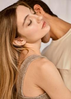 Vue latérale du couple intime embrassé