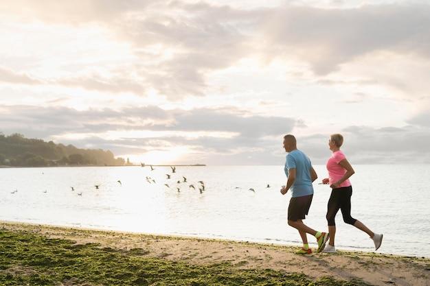 Vue latérale du couple de personnes âgées jogging sur la plage