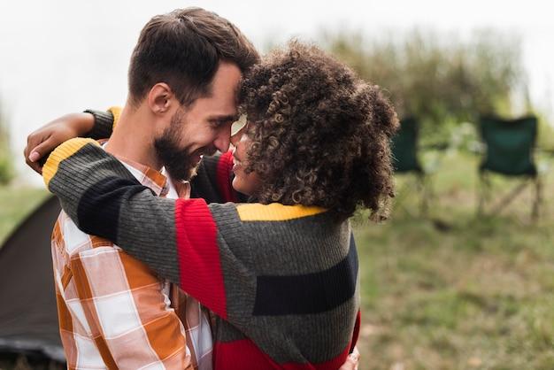 Vue latérale du couple romantique étreignant à l'extérieur