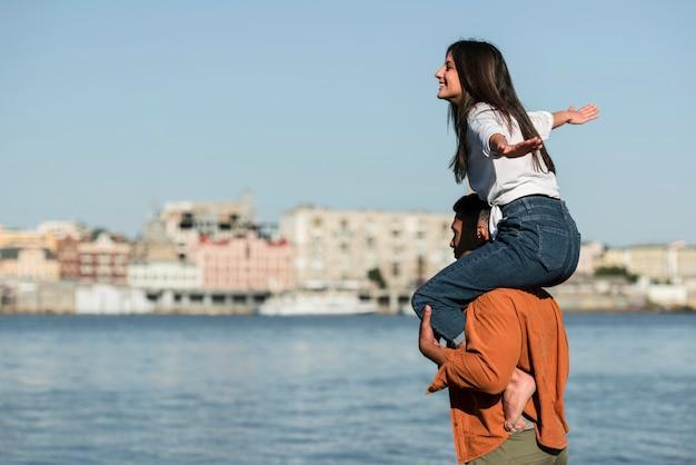Vue latérale du couple romantique profitant de la vue sur la plage