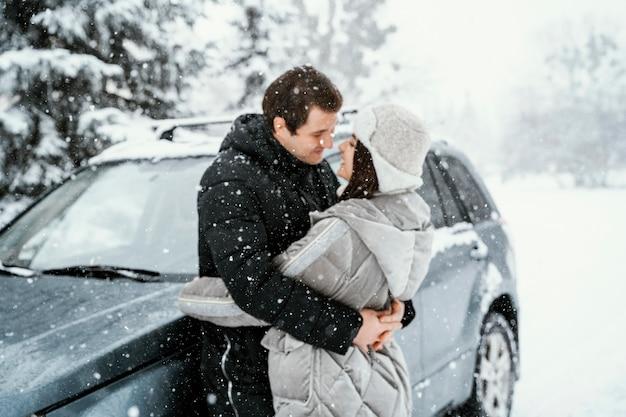 Vue latérale du couple romantique s'embrassant dans la neige lors d'un road trip