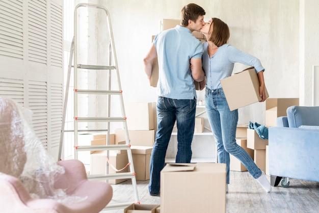 Vue latérale du couple s'embrassant lors de l'emballage pour sortir