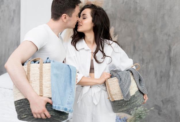 Vue latérale du couple se penchant pour un baiser tout en tenant des paniers