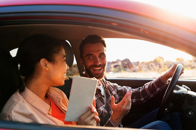 Vue latérale du couple smiley voyageant en voiture