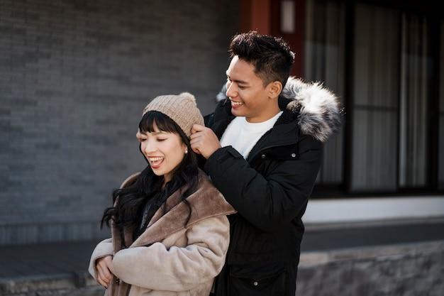 Vue latérale du couple souriant à l'extérieur