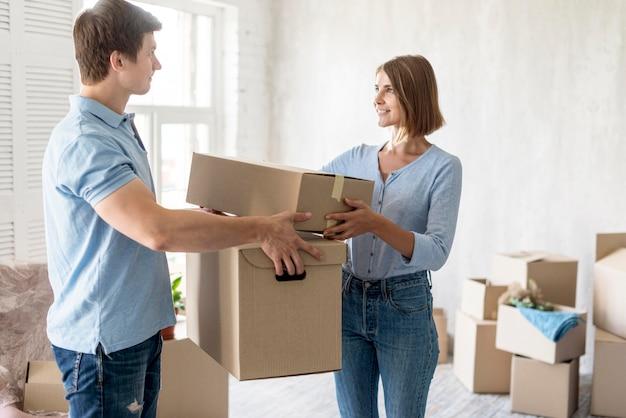 Vue latérale du couple tenant des boîtes de déménagement