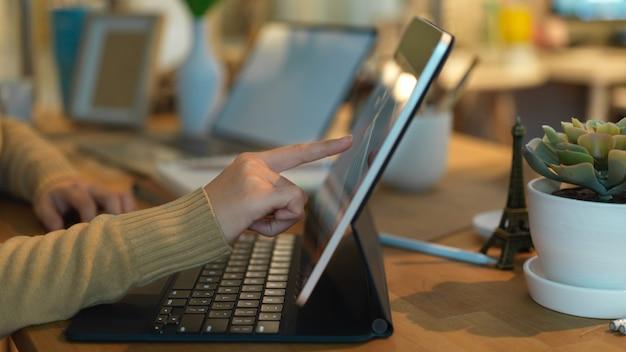 Vue latérale du doigt féminin pointant sur l'écran de l'ordinateur portable dans la salle de bureau