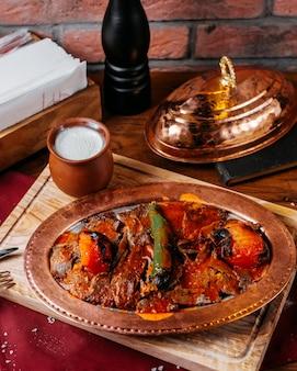 Vue latérale du doner traditionnel iskender turc avec du yogourt dans un pot en argile sur une planche de bois