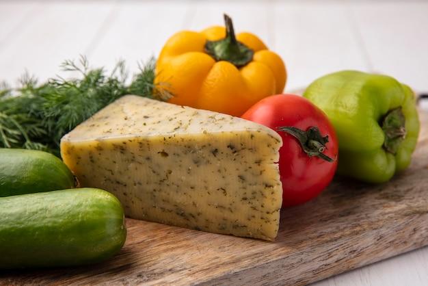 Vue latérale du fromage avec des concombres aux poivrons sur un support à l'aneth sur une plaque blanche